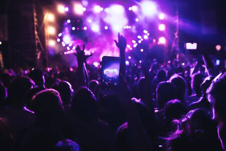 People taking photographs with touch smart phone during a music entertainment public concert.  live concert, music festival, happy youth, luxury party, landscape exterior. Selctive Focus