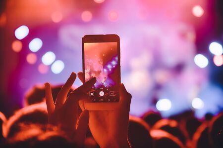 Personnes prenant des photos avec un smartphone tactile lors d'un concert public de divertissement musical. concert en direct, festival de musique, jeunesse heureuse, fête de luxe, extérieur paysager. Mise au point sélective