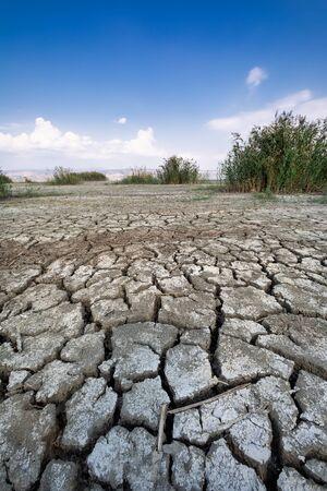 Lit de lac sec avec texture naturelle d'argile craquelée dans le sol en perspective. Champ de la Vallée de la Mort. Contexte. Mise au point sélective sur les terres sombres du sol noir. Idée concept symbole catastrophe écologie dans la nature