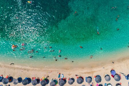 Aerial View From Flying Drone Of People Crowd Having Fun, Playing And Relaxing In Water At The Parga area, Ionian sea, Epirus, Greece