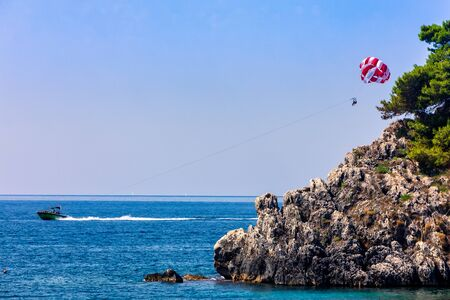 Parachute behind a boat on a summer holiday beach in Parga Epirus, Greece, Europe. Stock Photo