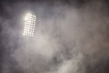 le stade de football allume des réflecteurs avec de la fumée. terrain de football