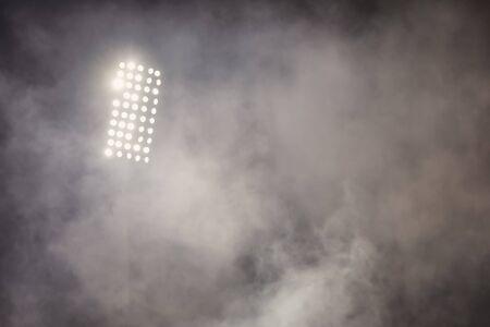 riflettori delle luci dello stadio di calcio con fumo. campo da calcio