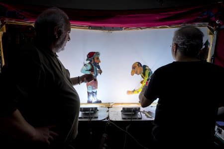 Thessaloniki, Greece - March 9, 2020: unidentified performers playing with the main character (Karagiozis) in the Greek shadow theatre behind the cotton screen during folk show.