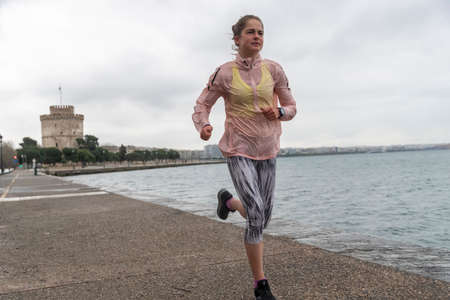 Thessaloniki, Greece - March 23, 2020: A woman jogging at Thessaloniki's port during lock down imposed by the government to prevent the further spread of the coronavirus