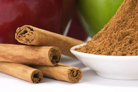 dietetical: Cinnamon barks and ground cinnamon with apples in the background. Stock Photo