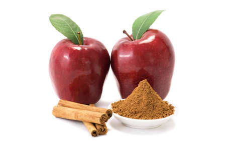 cinnamon bark: Two red delicious apples and cinnamon over white background.