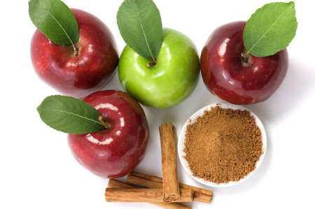 Four apples and cinnamon over white background photo