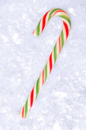 Candy cane against fake snow background. photo