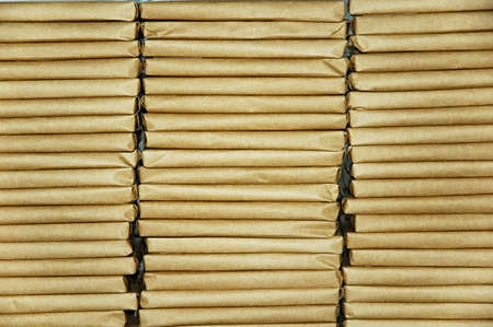 normal distribution: Flat parcels wrapped in brown paper arranged in three stacks Stock Photo