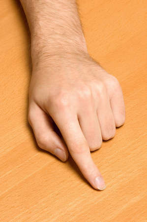 Male hand pointing at empty space on wooden table. photo