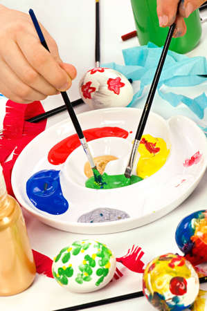 hand painting: Colourful paints on palette with brushes ready for painting easter eggs. Concept for art and craft classes. Stock Photo