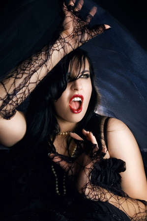 female vampire: Attractive female vampire screaming. Woman dressed up for halloween party. Stock Photo