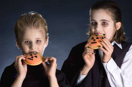 Boys dressed up for Halloween party eating Halloween cookies photo