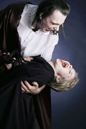 Father and son playing vampire and victim dressed up in Halloween costumes for a party.
