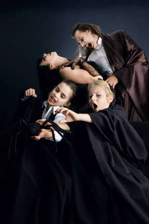 disguises: Four vampire family in action dressed up in Halloween costumes and having fun together. Stock Photo