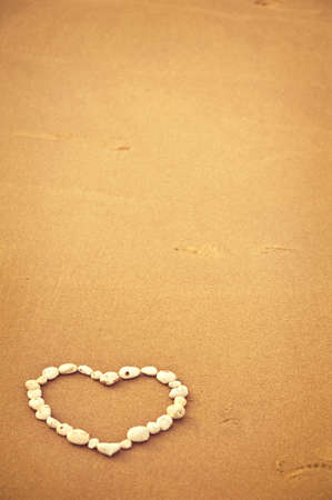 heart in sand: Heart made with white chalk pebbles on sand with plenty of copy space. Stock Photo