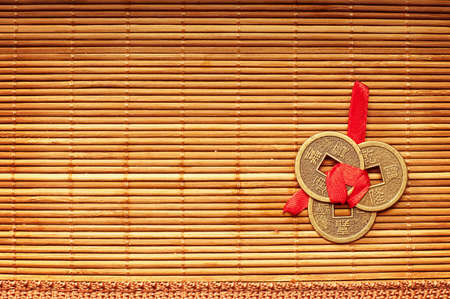 copper coin: Three Chinese lucky coins tied with red ribbon on wooden mat Stock Photo