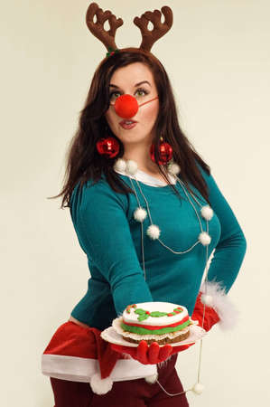 Funny photo of modern housewife in the Chtistmas spirit with the cake, dressed up with Christmas decorations.