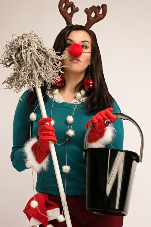 after work: Woman wearing festive decorations ready for cleaning after Christmas Stock Photo