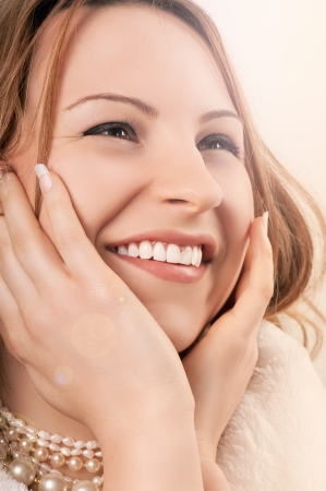 Beautiful happy young caucasian woman smiling showing her teeth while holding the face in her hands