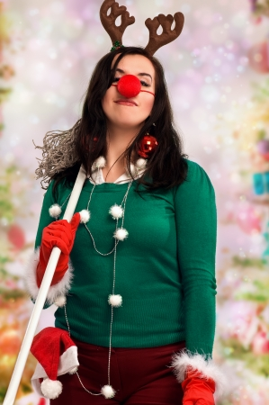 Woman wearing festive decorations and holding a mop ready for Christmas with colorful bokeh in the background