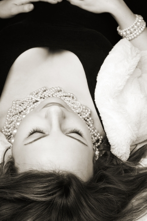 Black and white portrait of beautiful woman wearing pearls laying and relaxing with eyes closed