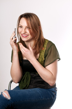 Beautiful young woman talking on the mobile phone and laughing