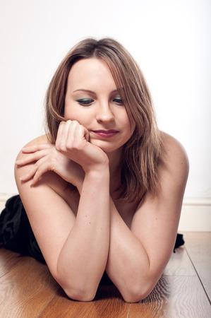 decission: Bella donna pensosa bionda posa sul pavimento, guardando verso il basso e sostenendo il mento con la mano sulla parete bianca Archivio Fotografico
