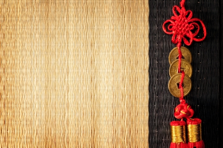 Background with three Chinese lucky coins tied with red cord on straw mat photo