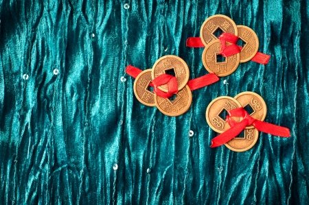 three sets of three Chinese lucky coins each tied with red ribbon on turquoise velvet fabric  One set of coins shows yin side while two others show yang