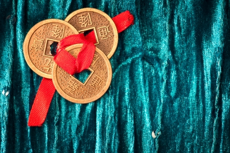 three Chinese lucky coins tied with red ribbon on turquoise velvet fabric