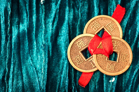 Blue velvet background with three Chinese lucky coins tied with red ribbon Stock Photo