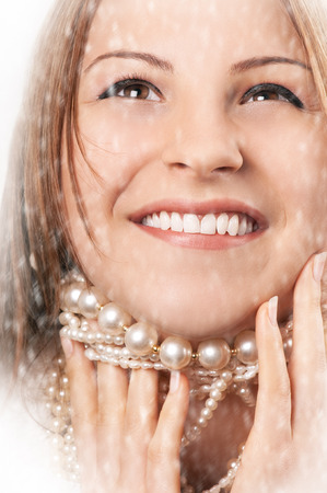 Beautiful happy young caucasian woman smiling in the snow and playing with her pearl necklace Stock Photo
