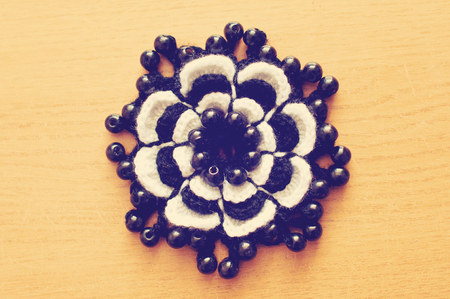 Crocheted black and white flower with wooden black beads on wooden table. Handmade decoration.