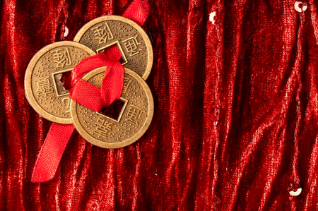 Background with three Chinese lucky coins tied with red ribbon on red velvet fabric Stock Photo