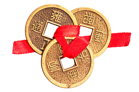 Three chinese lucky coins on yang side tied with red ribbon, isolated on white background. Symbol of wealth in feng-shui.