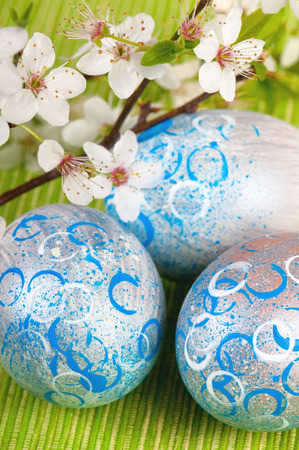 Easter eggs painted in silver with abstract, modern blue and white patterns, decorated with fresh plum blossom on green fabric.
