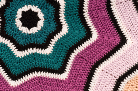 Crocheted, striped, star shaped blanket background. Detailed close-up of double crochet pattern.