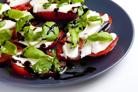 mozzarella, basil and tomatoes with olive oil and balsamic at the plate photo