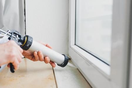 Handen van de werknemer met behulp van een siliconen buis voor het repareren van raam binnen