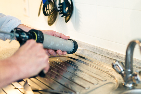 Hands of worker using a silicone tube  for repairing in the kitchen, indoor