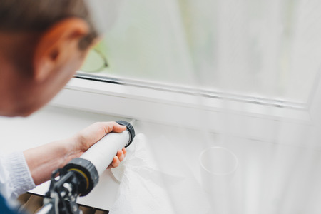 use pistol: Backview of old man using a silicone tube  for repairing the windowindoor Stock Photo