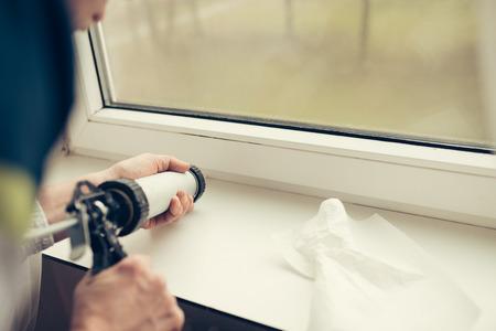 실내 창 수리를 위해 실리콘 튜브를 사용하는 작업자의 손 스톡 콘텐츠