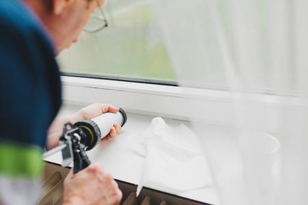 창 고를 수리하기 위해 실리콘 튜브를 사용하는 노인의 백 뷰