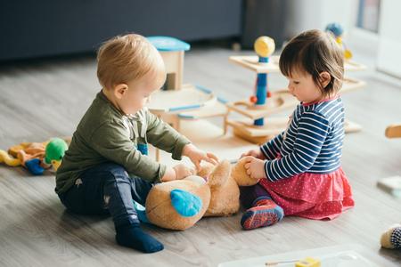 linda niña y niño jugando con juguetes en el hogar