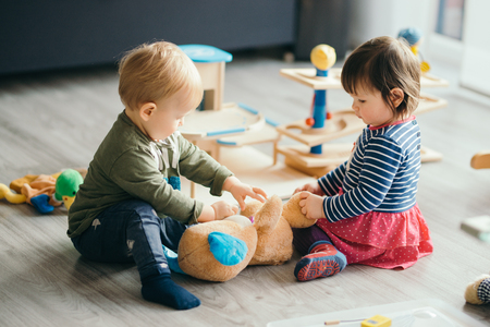 schattig klein meisje en jongen spelen met speelgoed bij het huis Stockfoto