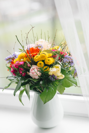 open windows: beautiful bouquet on windowsill at home Stock Photo