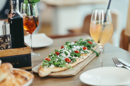 turkish pide with feta cheese, rucola and tomato, cocktails and sherbet in restaurant