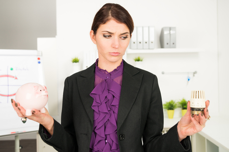 turn about: beautiful business  woman worry about heating bills holding a piggy bank